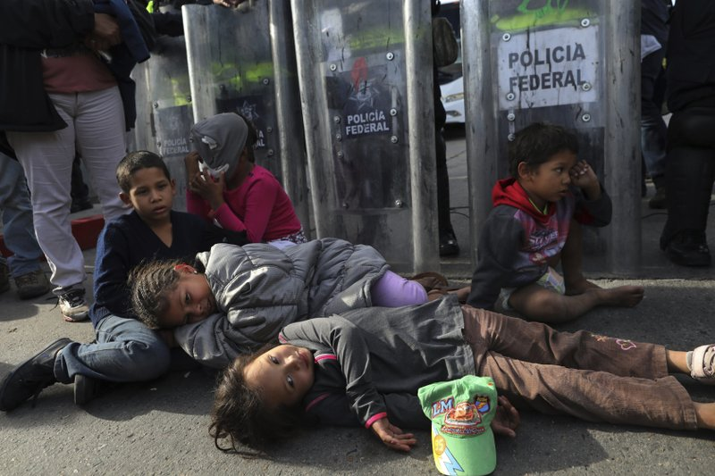 Migrant children rest on the ground in front of a line of Mexican police in riot gear, after they tried to cross the Chaparral border crossing in Tijuana, Mexico, Thursday, Nov. 22, 2018. The children, part of a group of Central American migrants, marched peacefully to the border crossing to demand better conditions and push to enter the U.S. (AP Photo/Rodrigo Abd)