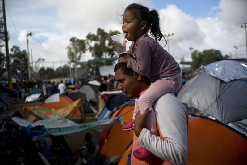 A man carries a girl on his shoulders at a migrant shelter in Tijuana, Mexico, Thursday, Nov. 22, 2018. Several thousand Central American migrants arrived in Tijuana last week more than a month after leaving Honduras in a caravan. (AP Photo/Ramon Espinosa)