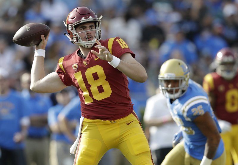 File-This Nov. 17, 2018, file photo shows Southern California quarterback JT Daniels (18) throwing against UCLA during the first half of an NCAA college football game in Pasadena, Calif. The Trojans have plenty of motivation of their own in the 90th edition of this famed intersectional rivalry, however. They're definitely playing for bowl eligibility, and they could be playing for Clay Helton's job as they wrap up USC's worst regular season since 2000. (AP Photo/Marcio Jose Sanchez, File)