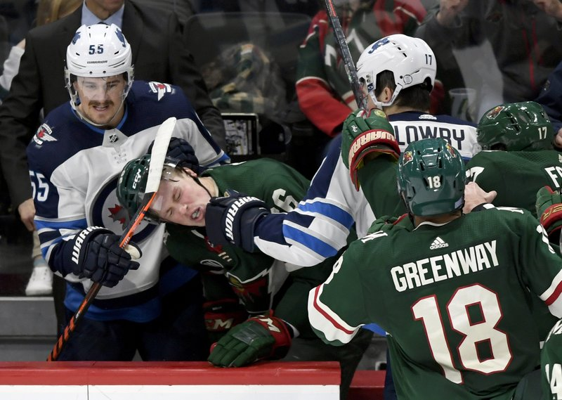 Winnipeg Jets' Adam Lowry (17) punches Minnesota Wild's Nick Seeler (36) in the Jets bench as Jets' Mark Scheifele (55) watches during the third period of an NHL hockey game Friday, Nov. 23, 2018, in St. Paul, Minn. The Wild won 4-2. (AP Photo/Hannah Foslien)