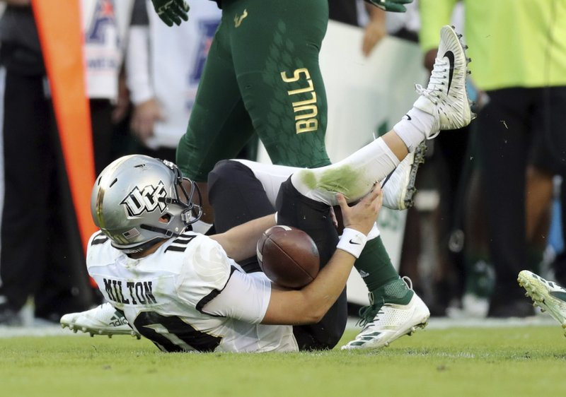 Central Florida quarterback McKenzie Milton goes down with an apparent knee injury after being tackled during the first half of an NCAA college football game against South Florida on Friday, Nov. 23, 2018, in Tampa, Fla. (AP Photo/Mike Carlson)