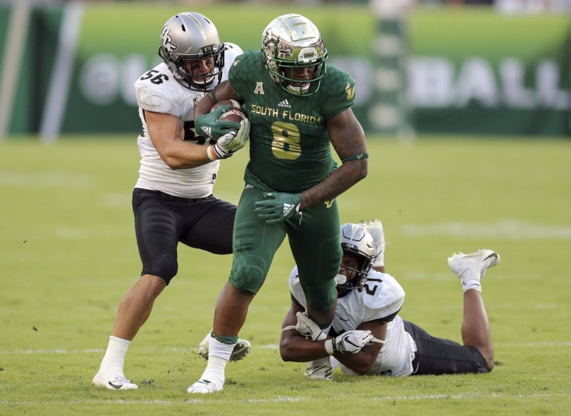South Florida's Tyre McCants (8) is tackled by Central Florida's Pat Jasinski (56) and Rashard Causey (21) during the first half of an NCAA college football game Friday, Nov. 23, 2018, in Tampa, Fla. (AP Photo/Mike Carlson)