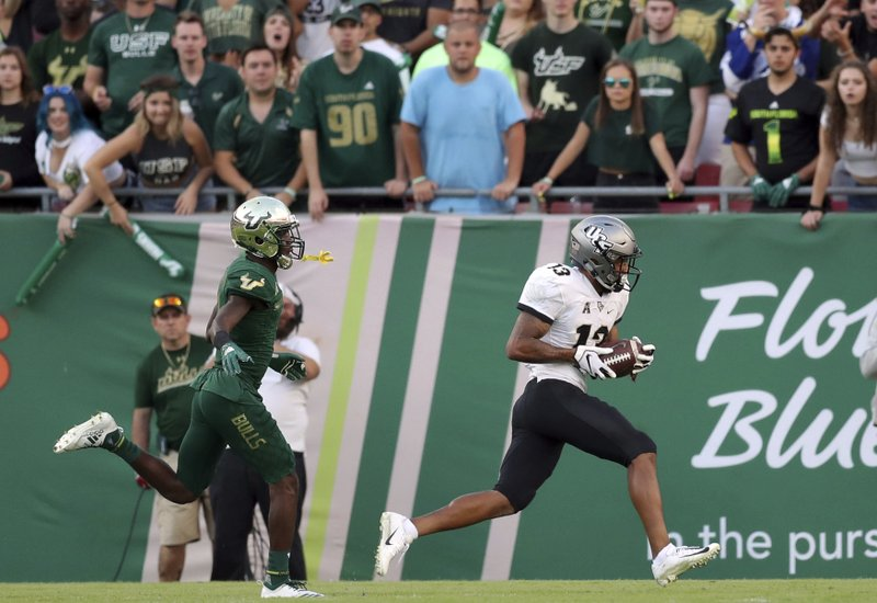 Central Florida's Gabriel Davis catches a touchdown pass behind South Florida's Mike Hampton during the first half of an NCAA college football game Friday, Nov. 23, 2018, in Tampa, Fla. (AP Photo/Mike Carlson)