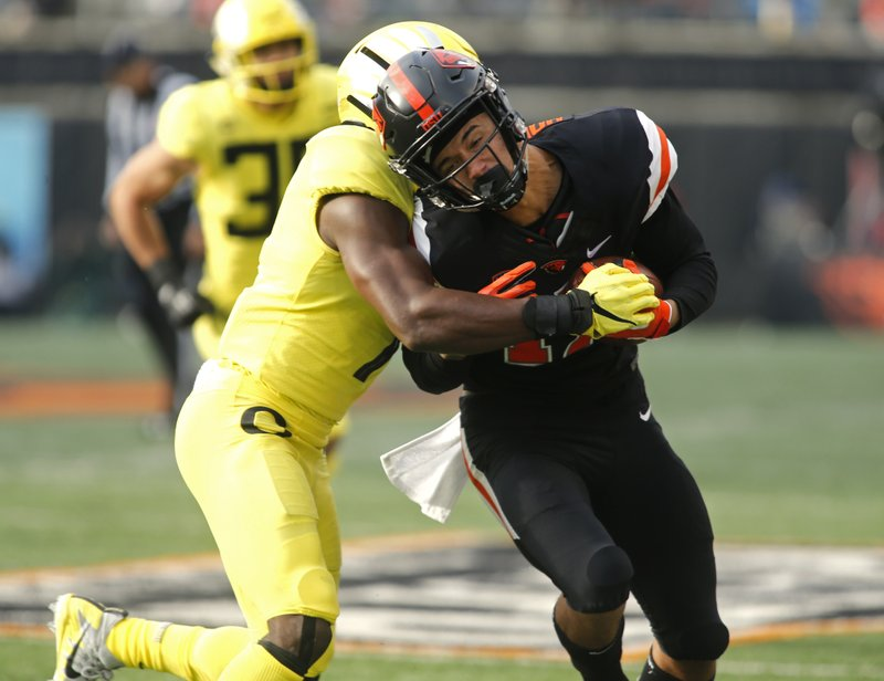Oregon State wide receiver Isaiah Hodgins, right, is hit by Oregon's Ugochukwu Amadi, left, after making a catch in the first half of an NCAA football game in Corvallis, Ore., Friday, Nov. 23, 2018. (AP Photo/Timothy J. Gonzalez)