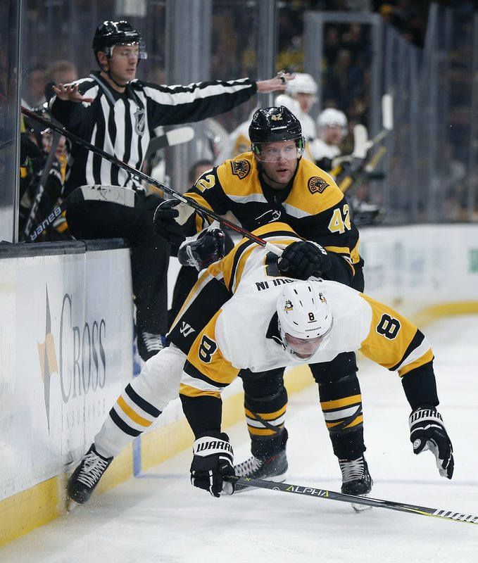 Boston Bruins' David Backes (42) checks Pittsburgh Penguins' Brian Dumoulin (8) during the second period of an NHL hockey game in Boston, Friday, Nov. 23, 2018. (AP Photo/Michael Dwyer)