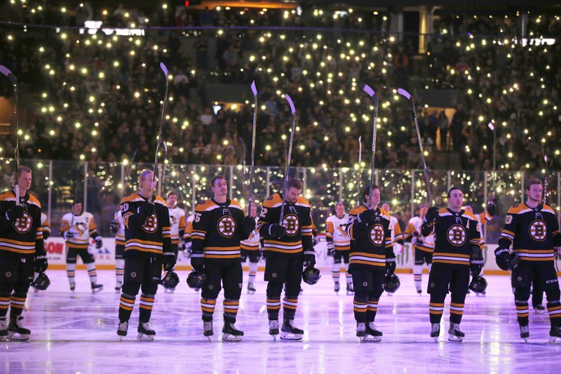 The Boston Bruins and the Pittsburgh Penguins stand on the ice during a tribute to cancer patients and survivors before an NHL hockey game in Boston, Friday, Nov. 23, 2018. (AP Photo/Michael Dwyer)
