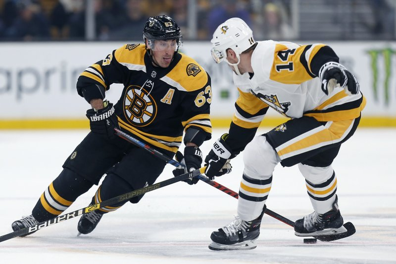 Boston Bruins' Brad Marchand (63) makes a move past Pittsburgh Penguins' Tanner Pearson (14) during the second period of an NHL hockey game in Boston, Friday, Nov. 23, 2018. (AP Photo/Michael Dwyer)