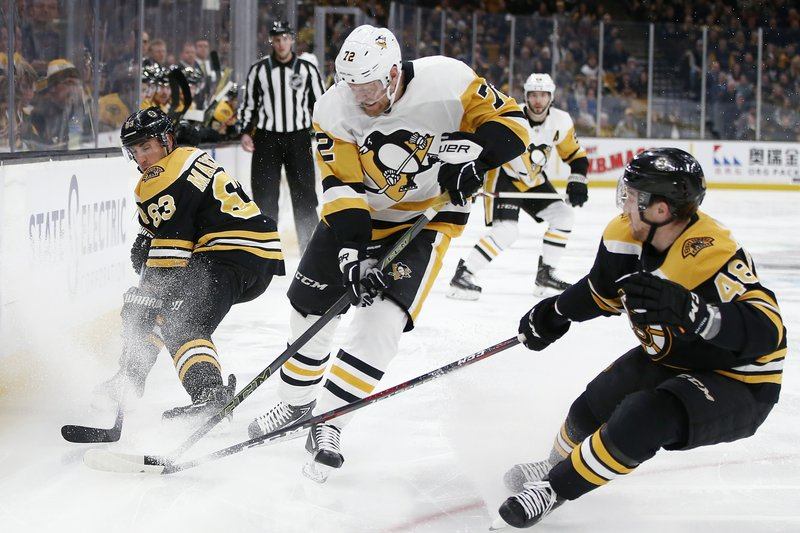 Pittsburgh Penguins' Patric Hornqvist (72) battles Boston Bruins' Brad Marchand (63) and Matt Grzelcyk (48) for the puck during the first period of an NHL hockey game in Boston, Friday, Nov. 23, 2018. (AP Photo/Michael Dwyer)