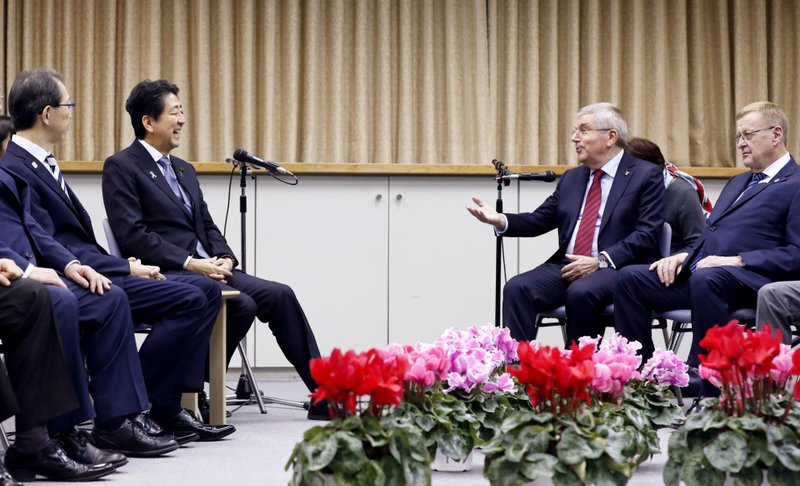 IOC President Thomas Bach, second from right, and Japanese Prime Minister Shinzo Abe, second from left, hold a talk in Fukushima, northeastern Japan, Saturday, Nov. 24, 2018. Bach and Abe made a quick trip Saturday, to the region northeast of Tokyo that was devastated by a 2011 earthquake and tsunami that destroyed three nuclear reactors.(Kyodo News via AP)