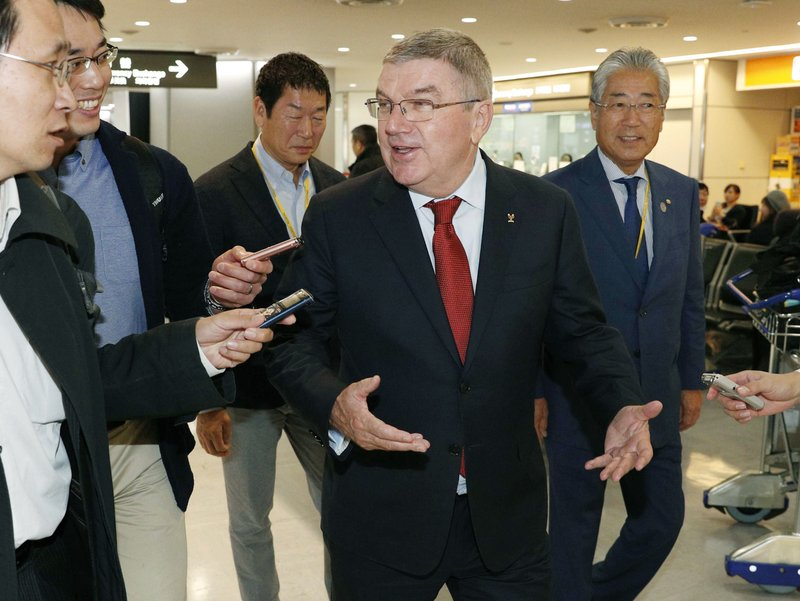 In this Nov. 23, 2018, photo, IOC President Thomas Bach, center, arrives at Narita Airport, near Tokyo. IOC President Bach and Japanese Prime Minister Shinzo Abe made a quick trip Saturday, Nov. 24, 2018, to the region northeast of Tokyo that was devastated by a 2011 earthquake and tsunami that destroyed three nuclear reactors. At right is Tsunekazu Takeda, an IOC member and head of the Japanese Olympic Committee. (Kyodo News via AP)