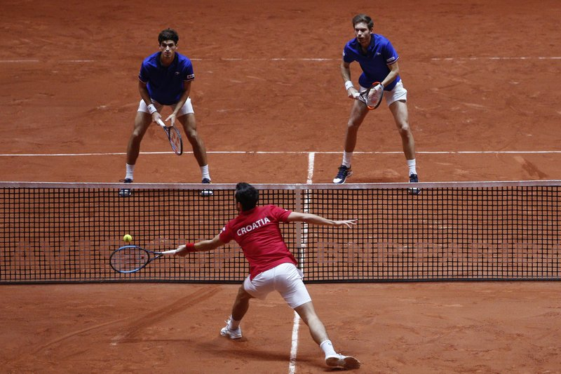 Mate Pavic of Croatia, bottom, returns the ball to France's Nicolas Mahut, right, and Pierre Hughes Herbert during the Davis Cup final between France and Croatia, Saturday, Nov. 24, 2018 in Lille, northern France. Croatia is within one point of a second Davis Cup title after Borna Coric and Marin Cilic dispatched their French rivals in the opening singles matches of the final to take a 2-0 lead. (AP Photo/Thibault Camus)