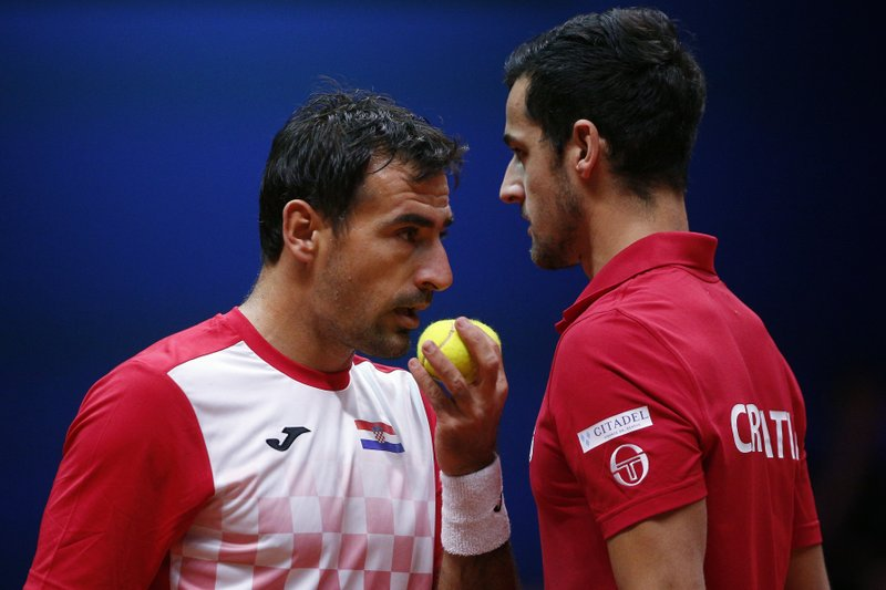 Croatia's Ivan Dodig, left, and Mate Pavic talk during the Davis Cup final between France and Croatia, Saturday, Nov. 24, 2018 in Lille, northern France. Croatia is within one point of a second Davis Cup title after Borna Coric and Marin Cilic dispatched their French rivals in the opening singles matches of the final to take a 2-0 lead. (AP Photo/Thibault Camus)