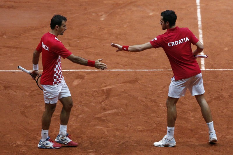 Croatia's Ivan Dodig, left, and Mate Pavic in their Davis Cup final between France and Croatia, Saturday, Nov. 24, 2018 in Lille, northern France. Croatia is within one point of a second Davis Cup title after Borna Coric and Marin Cilic dispatched their French rivals in the opening singles matches of the final to take a 2-0 lead. (AP Photo/Thibault Camus)