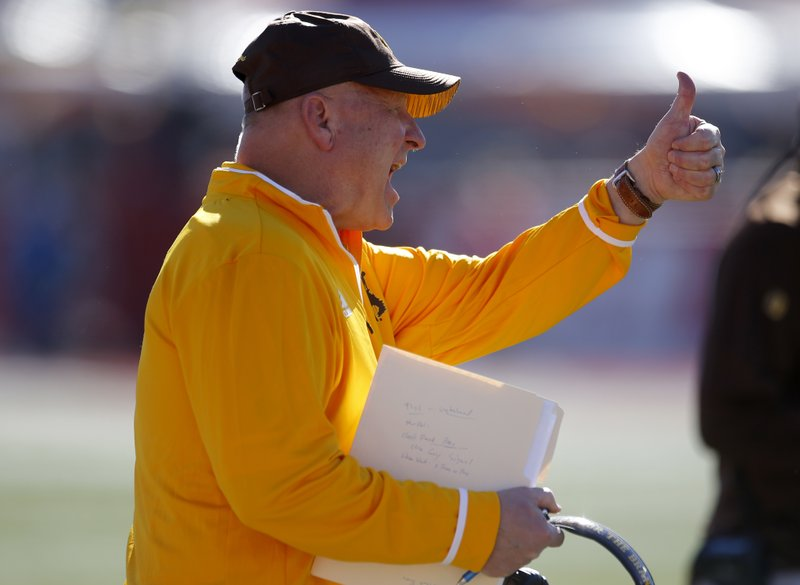 Wyoming coach Craig Bohl gives a thumbs up to his players during the first half of an NCAA college football game against New Mexico in Albuquerque, N.M., Saturday, Nov. 24, 2018. (AP Photo/Andres Leighton)