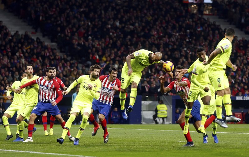 Barcelona's Arturo Vidal center jumps for the ball leaving his arm in the way during a Spanish La Liga soccer match between Atletico Madrid and FC Barcelona at the Metropolitano stadium in Madrid, Saturday, Nov. 24, 2018. (AP Photo/Paul White)
