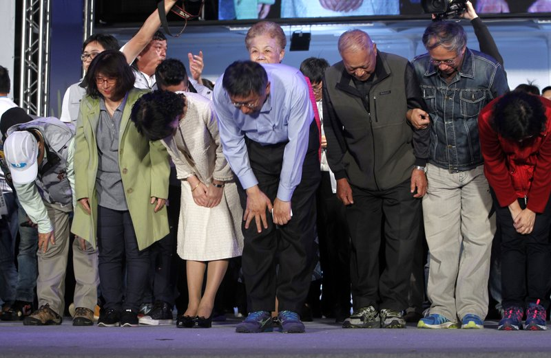 Taipei city mayor and city mayoral candidate Ko Wen-je, center, Ko's families, team members bow to supporters for winning in Taipei, Taiwan, Sunday early morning, Nov. 25, 2018. Taiwan's ruling party suffered a major defeat Saturday in local elections seen as a referendum on the administration of the island's independence-leaning president amid growing economic and political pressure from China. (AP Photo/Chiang Ying-ying)