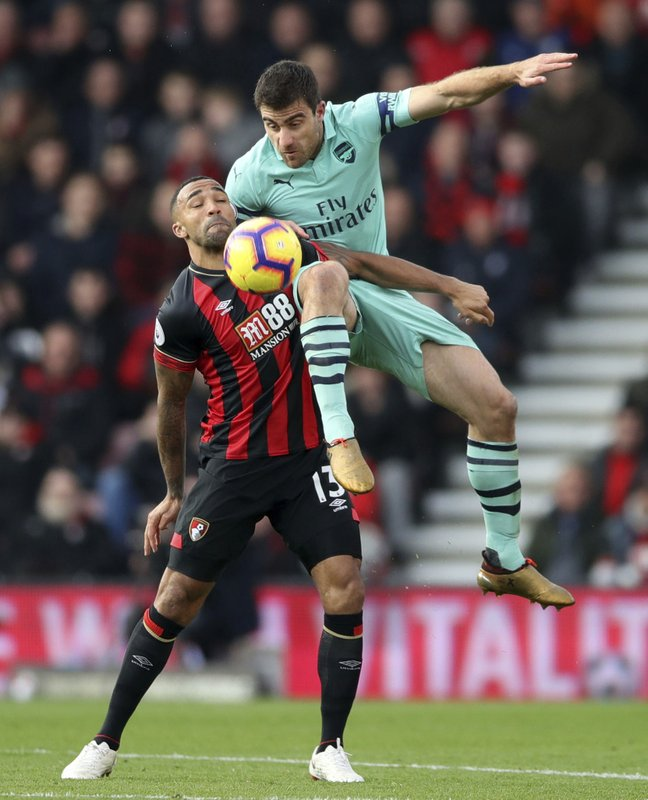 Arsenal's Sokratis Papastathopoulos, top, and Bournemouth's Callum Wilson in action during their English Premier League soccer match at The Vitality Stadium in Bournemouth, England, Sunday Nov. 25, 2018. (John Walton/PA via AP)