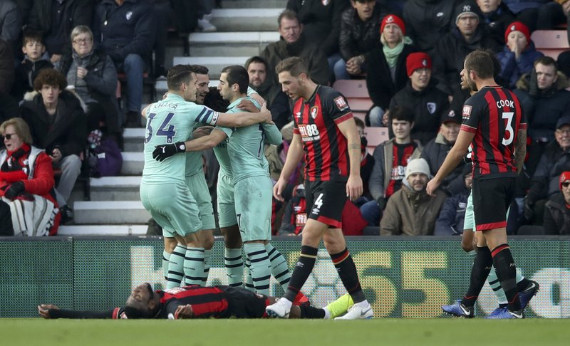 Bournemouth's Jefferson Lerma lays on the ground dejected after conceding an own goal as Arsenal players celebrate, during a Premier League soccer match between Bournemouth and Arsenal, at The Vitality Stadium, Bournemouth, Sunday, Nov. 25, 2018. (John Walton/PA via AP)