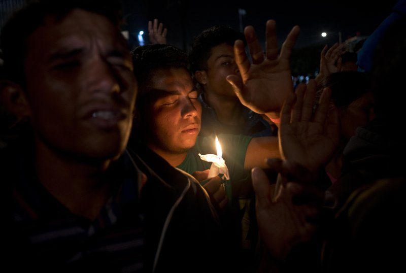 Migrants pray during a vigil outside the Benito Juarez Sports Center serving as a temporary shelter for Central American migrants in Tijuana, Mexico, Saturday, Nov. 24, 2018. The mayor of Tijuana has declared a humanitarian crisis in his border city and says that he has asked the United Nations for aid to deal with the approximately 5,000 Central American migrants who have arrived in the city. (AP Photo/Ramon Espinosa)