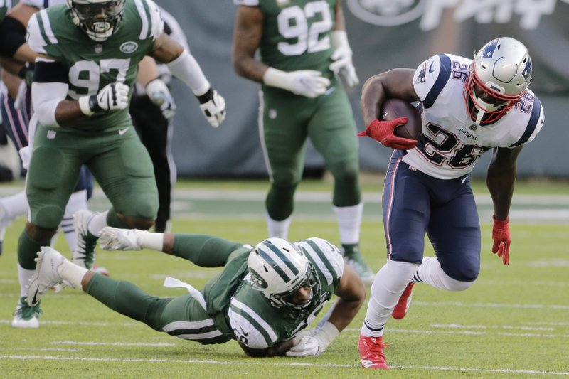 New England Patriots' Sony Michel (26) breaks a tackle by New York Jets' Frankie Luvu (50) during the second half of an NFL football game Sunday, Nov. 25, 2018, in East Rutherford, N.J. (AP Photo/Seth Wenig)