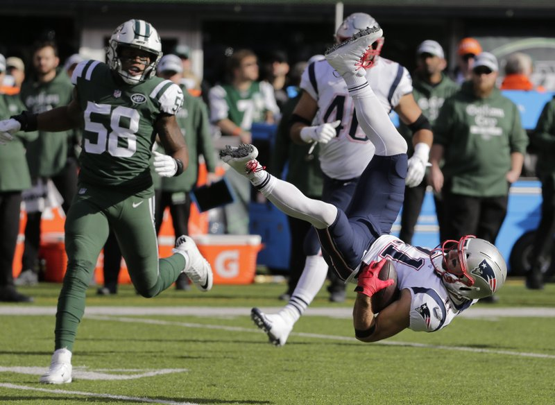 New York Jets inside linebacker Darron Lee (58) watches as New England Patriots' Julian Edelman (11) flips after being hit by teammate Darryl Roberts during the first half of an NFL football game Sunday, Nov. 25, 2018, in East Rutherford, N.J. (AP Photo/Seth Wenig)