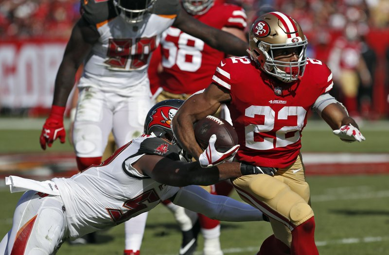 San Francisco 49ers running back Matt Breida (22) slips a tackle by Tampa Bay Buccaneers outside linebacker Adarius Taylor (53) during the first half of an NFL football game Sunday, Nov. 25, 2018, in Tampa, Fla. (AP Photo/Mark LoMoglio)