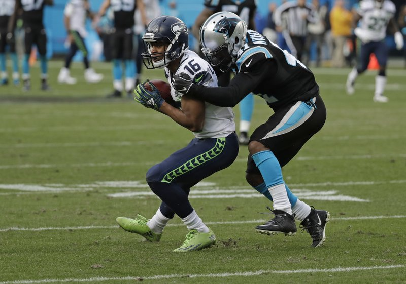 Seattle Seahawks' Tyler Lockett (16) catches a pass against Carolina Panthers' Captain Munnerlyn (41) during the second half of an NFL football game in Charlotte, N.C., Sunday, Nov. 25, 2018. (AP Photo/Chuck Burton)