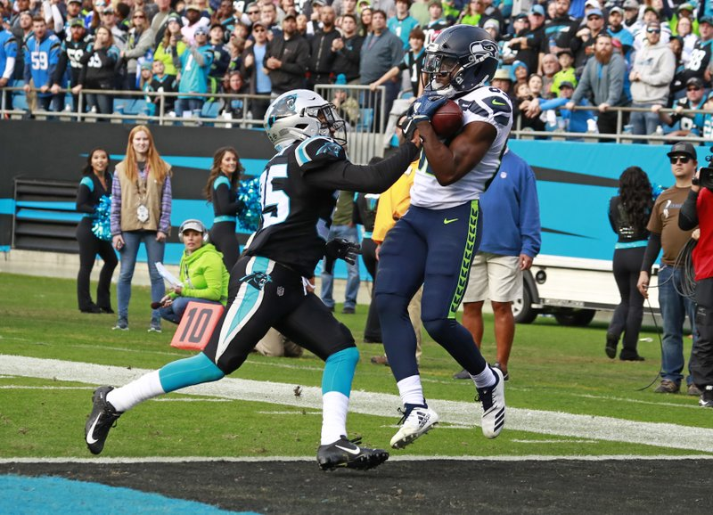 Seattle Seahawks' David Moore (83) catches a touchdown pass as Carolina Panthers' Corn Elder (35) defends during the second half of an NFL football game in Charlotte, N.C., Sunday, Nov. 25, 2018. (AP Photo/Jason E. Miczek)