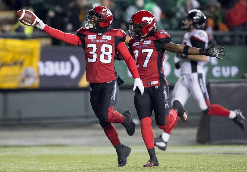 Calgary Stampeders running back Terry Williams (38) celebrates a punt return for a touchdown against the Ottawa Redblacks, with defensive back Tunde Adeleke (27) during the first half of the Canadian Football League Grey Cup in Edmonton, Alberta, Sunday, Nov. 25, 2018. (Darryl Dyck/The Canadian Press via AP)