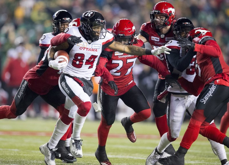 Calgary Stampeders try to stop Ottawa Redblacks wide receiver R.J. Harris (84) during the second half of the Canadian Football League Grey Cup in Edmonton, Alberta, Sunday, Nov. 25, 2018. (Darryl Dyck/The Canadian Press via AP)
