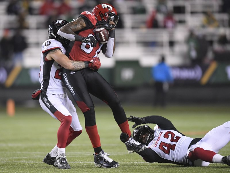 Calgary Stampeders wide receiver Chris Matthews (81) gets tackled by Ottawa Redblacks defensive back Anthony Cioffi (24) and linebacker Avery Williams (42) during the second half of the Canadian Football League Grey Cup in Edmonton, Alberta, Sunday, Nov. 25, 2018. (Nathan Denette/The Canadian Press via AP)