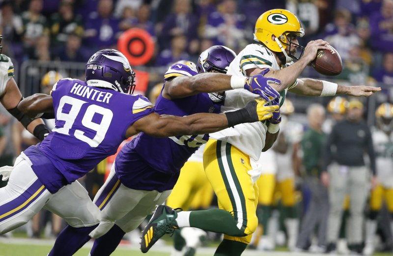 Green Bay Packers quarterback Aaron Rodgers is sacked by Minnesota Vikings defenders Danielle Hunter (99) and Tom Johnson, center during the first half of an NFL football game, Sunday, Nov. 25, 2018, in Minneapolis. (AP Photo/Bruce Kluckhohn)