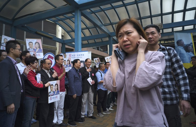 """In this Sunday, Nov. 25, 2018 photo, a local resident, right, walks past supporters of establishment candidate Chan Hoi-yan during a by-election campaign at the voting day in Hong Kong.  Voters in China's semi-autonomous region of Hong Kong elected a pro-establishment politician to the legislature in a by-election called after the incumbent was ejected from the body for """"improper oath taking,"""" one of six pro-democracy legislators ousted on that charge. Chan's sizable victory in the Kowloon West constituency ends the opposition's hopes of regaining veto power in the assembly and continues to reduce the influence of the pro-democracy camp that has been shrinking since widespread 2014 demonstrations fizzled out with little result. (AP Photo/Vincent Yu)"""