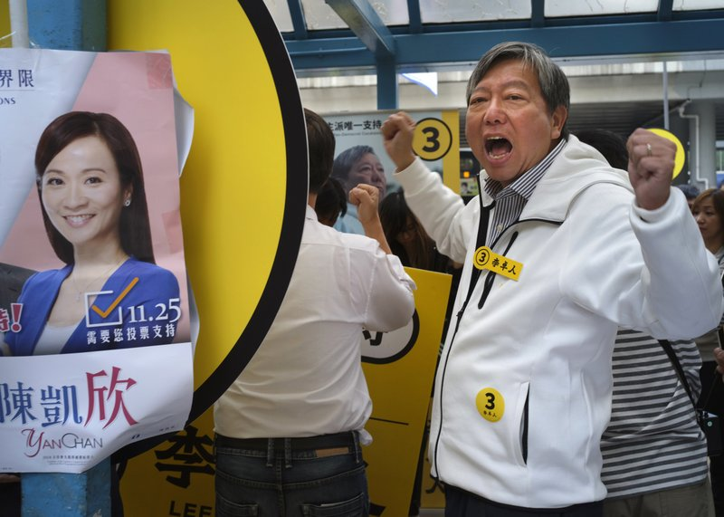 In this Sunday, Nov. 25, 2018 photo, Pro-democracy candidate Lee Cheuk-yan, right, shouts slogans next to an election poster of establishment candidate Chan Hoi-yan during a by-election campaign at the voting day in Hong Kong. Elections over the weekend in self-governing Taiwan and the Chinese-controlled territory of Hong Kong displayed vastly different visions of a democratic future, with strong implications for Beijing's ambitions of asserting its control over the entire Chinese-speaking world. (AP Photo/Vincent Yu)