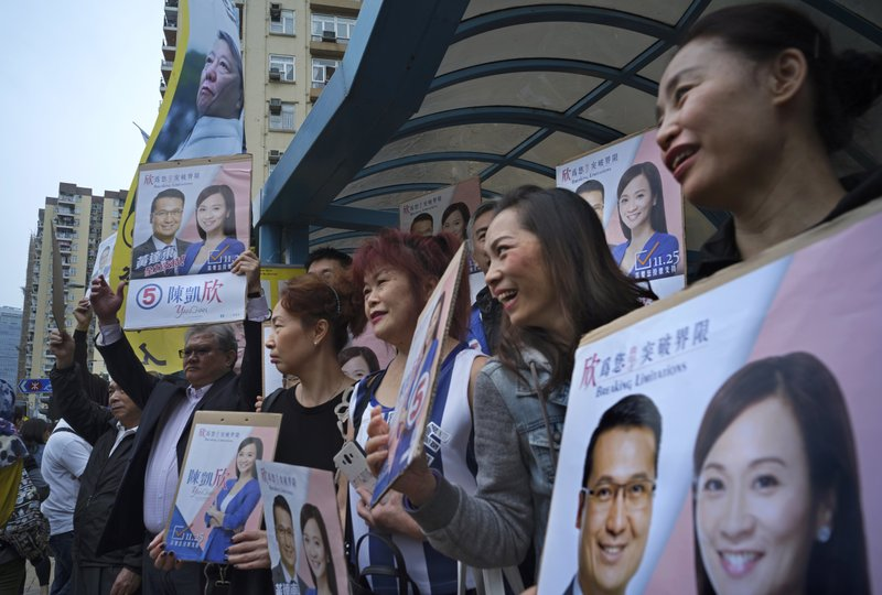 In this Sunday, Nov. 25, 2018 photo, supporters of establishment candidate Chan Hoi-yan hold placards in front of a banner of Pro-democracy candidate Lee Cheuk-yan, top left, during a by-election campaign at the voting day in Hong Kong. Chan's sizable victory in the Kowloon West constituency ends the opposition's hopes of regaining veto power in the assembly and continues to reduce the influence of the pro-democracy camp that has been shrinking since widespread 2014 demonstrations fizzled out with little result.(AP Photo/Vincent Yu)