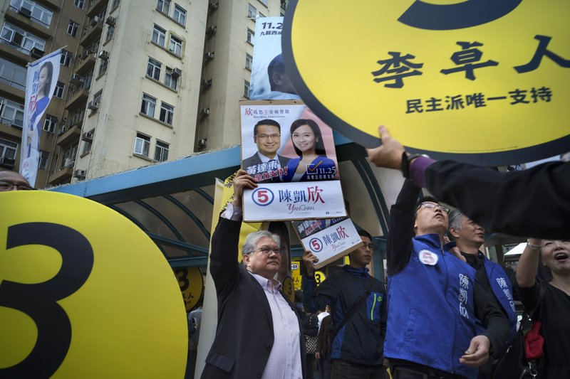 In this Sunday, Nov. 25, 2018 photo, supporters of establishment candidate Chan Hoi-yan raise election posters behind placards, yellow, of Pro-democracy candidate Lee Cheuk-yan during a by-election campaign at the voting day in Hong Kong. Chan's sizable victory in the Kowloon West constituency ends the opposition's hopes of regaining veto power in the assembly and continues to reduce the influence of the pro-democracy camp that has been shrinking since widespread 2014 demonstrations fizzled out with little result. (AP Photo/Vincent Yu)