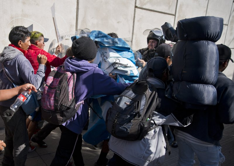 Migrants push past Mexican police at the Chaparral border crossing in Tijuana, Mexico, Sunday, Nov. 25, 2018, as they try to reach the United States. The mayor of Tijuana has declared a humanitarian crisis in his border city and says that he has asked the United Nations for aid to deal with the approximately 5,000 Central American migrants who have arrived in the city. (AP Photo/Ramon Espinosa)