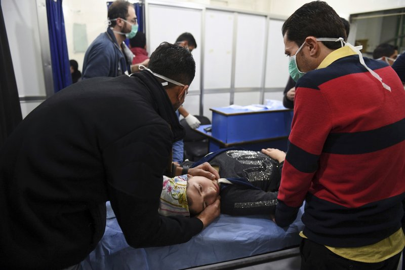In this photo released by the Syrian official news agency SANA, a woman receives treatment at a hospital following a suspected poison gas attack on her town of al-Khalidiya, in Aleppo, Syria, Saturday, Nov. 24, 2018. At least 50 civilians were being treated Saturday following a suspected poison gas attack by Syrian rebel groups on the government-held Aleppo city in the country's north, according to reports in Syrian state media. (SANA via AP)