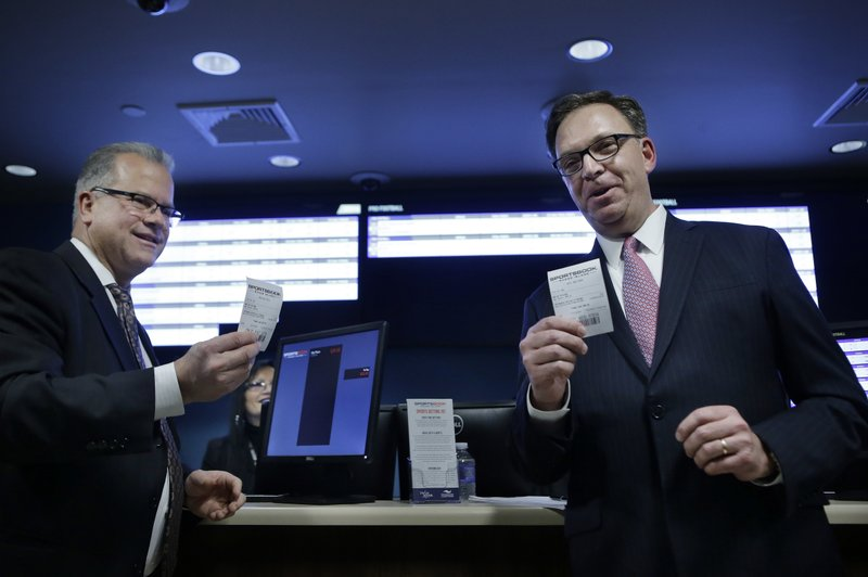 Rhode Island Democratic House Speaker Nicholas Mattiello, left, and John Taylor, chairman of Twin River Worldwide Holdings, right, display tickets after placing bets on sporting events during a ceremony, Monday, Nov. 26, 2018, at Twin River Casino Hotel, in Lincoln, R.I. Rhode Island is the first New England state to legalize sports betting since the U.S. Supreme Court struck down a federal law this year that made most sports gambling illegal. (AP Photo/Steven Senne)