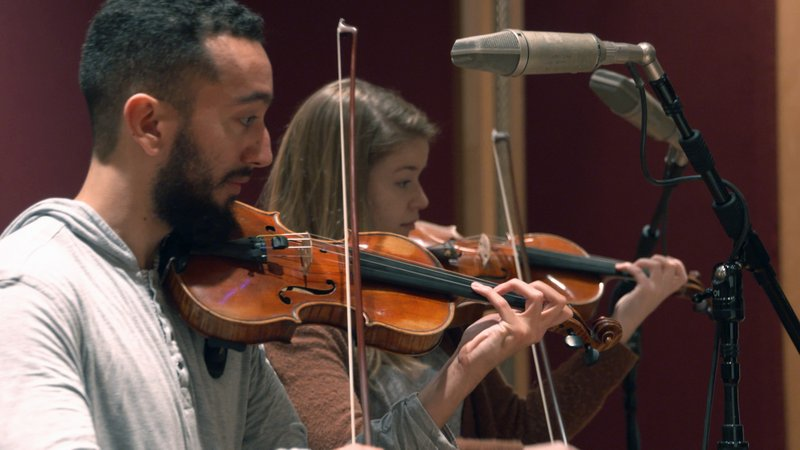 In this Nov. 7, 2018, photo provided by the University of Michigan, student violinists Reuben Kebede and Dana Johnson perform at a recording session in Ann Arbor, Mich., with Contemporary Directions Ensemble recording