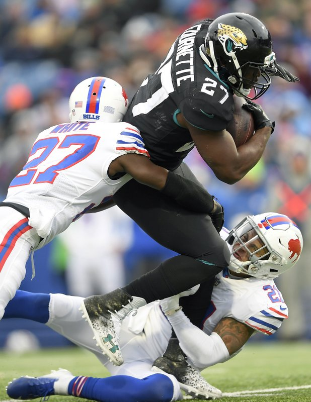 Jacksonville Jaguars running back Leonard Fournette (27) is tackled by Buffalo Bills cornerback Tre'Davious White (27) and free safety Jordan Poyer (21) during the first half of an NFL football game, Sunday, Nov. 25, 2018, in Orchard Park, N.Y. (AP Photo/Adrian Kraus)