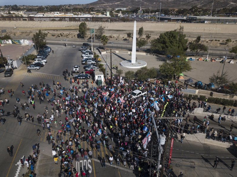 A group of migrants gather at the Chaparral border crossing in Tijuana, Mexico, Sunday, Nov. 25, 2018, as they try to pressure their way into the U.S. The mayor of Tijuana has declared a humanitarian crisis in his border city and says that he has asked the United Nations for aid to deal with the approximately 5,000 Central American migrants who have arrived in the city. (AP Photo/Rodrigo Abd)