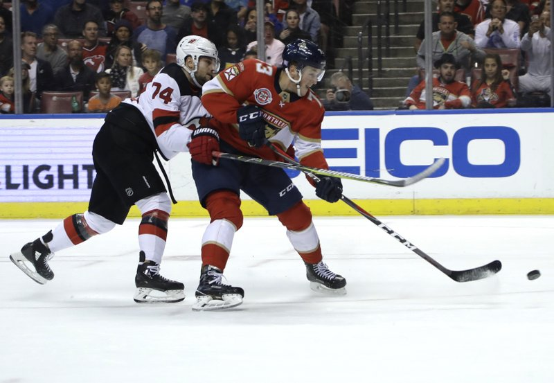 Florida Panthers left wing Dryden Hunt (73) takes a shot on goal as New Jersey Devils defenseman Egor Yakovlev defends during the second period of an NHL hockey game, Monday, Nov. 26, 2018, in Sunrise, Fla. (AP Photo/Lynne Sladky)
