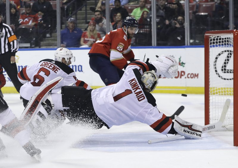 New Jersey Devils goaltender Keith Kinkaid (1) stops the puck as Florida Panthers defenseman Aaron Ekblad (5) looks on during the first period of an NHL hockey game, Monday, Nov. 26, 2018, in Sunrise, Fla. (AP Photo/Lynne Sladky)