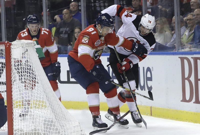 Florida Panthers right wing Juho Lammikko (91) and New Jersey Devils defenseman Egor Yakovlev (74) go for the puck as a loose stick lies on the ice during the first period of an NHL hockey game, Monday, Nov. 26, 2018, in Sunrise, Fla. (AP Photo/Lynne Sladky)