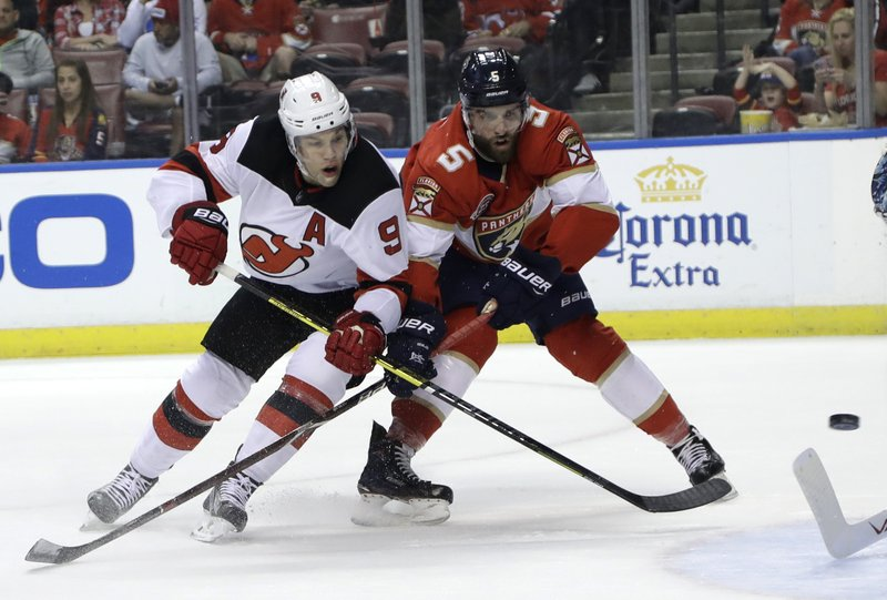 New Jersey Devils left wing Taylor Hall (9) and Florida Panthers defenseman Aaron Ekblad (5) go for the puck during the first period of an NHL hockey game, Monday, Nov. 26, 2018, in Sunrise, Fla. (AP Photo/Lynne Sladky)