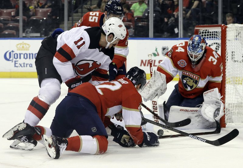 Florida Panthers goaltender James Reimer (34) stops the puck as New Jersey Devils center Brian Boyle (11) and defenseman MacKenzie Weegar (52) look on during the first period of an NHL hockey game, Monday, Nov. 26, 2018, in Sunrise, Fla. (AP Photo/Lynne Sladky)