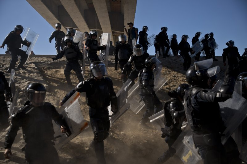 Mexican police run as they try to keep migrants from getting past the Chaparral border crossing in Tijuana, Mexico, Sunday, Nov. 25, 2018, near San Ysidro, California. The mayor of Tijuana has declared a humanitarian crisis in his border city and says that he has asked the United Nations for aid to deal with the approximately 5,000 Central American migrants who have arrived in the city. (AP Photo/Ramon Espinosa)