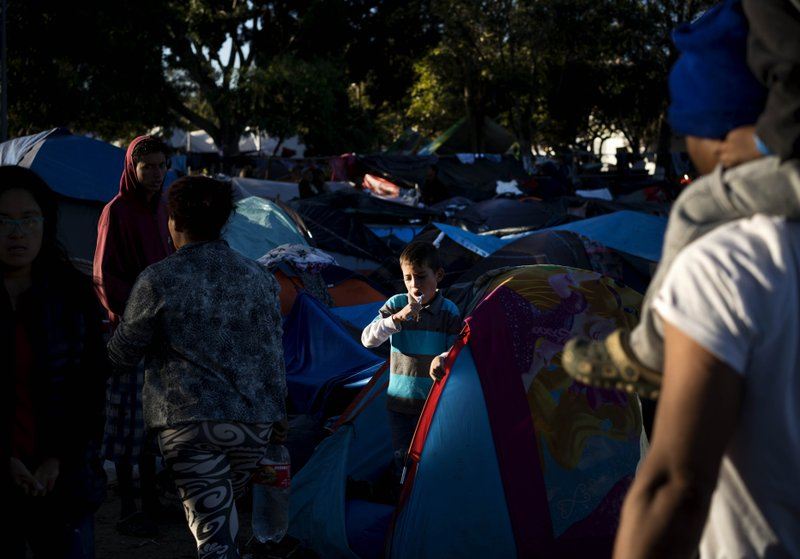 A young member of a migrant caravan brushes his teeth inside his tent at the Benito Juarez Sports Center that is serving as a shelter for migrants in Tijuana, Mexico, Monday, Nov. 26, 2018. The mayor of Tijuana has declared a humanitarian crisis in his border city and says that he has asked the United Nations for aid to deal with thousands of Central American migrants who have arrived. (AP Photo/Ramon Espinosa)