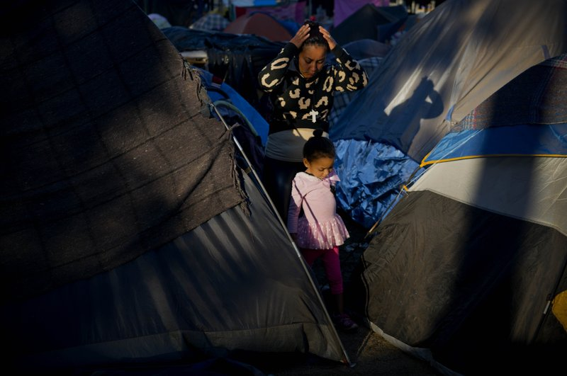 A woman and a girl who traveled a caravan of migrants walks between tents at the Benito Juarez Sports Center which is serving as a shelter in Tijuana, Mexico, Monday, Nov. 26, 2018. The mayor of Tijuana has declared a humanitarian crisis in his border city and says that he has asked the United Nations for aid to deal with thousands of Central American migrants who have arrived. (AP Photo/Ramon Espinosa)